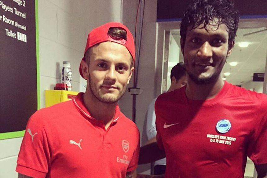 Singapore Selection defender Madhu Mohana cannot hide his delight as he poses with Arsenal midfielder Jack Wilshere.