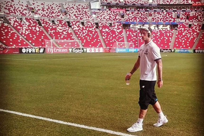 Stoke forward Marko Arnautovic gets a feel of the National Stadium pitch ahead of their Barclays Asia Trophy match against the Singapore Selection.