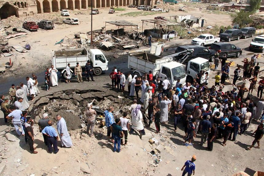Iraqis gather around a hole caused by a bomb attack a day earlier at Khan bani Saad town, eastern Baghdad, Iraq, on July 18, 2015.