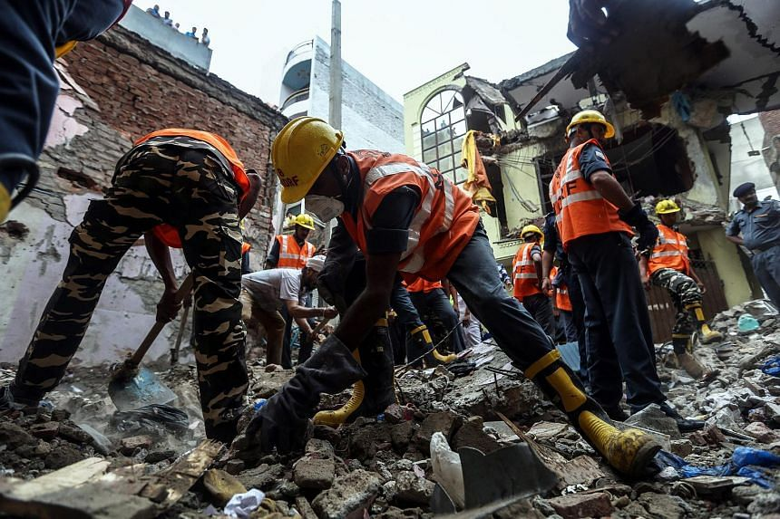 Rescue workers sifting through rubble after a multi-storey residential building collapsed in Vishnu Garden in Delhi, India, on July 19, 2015.