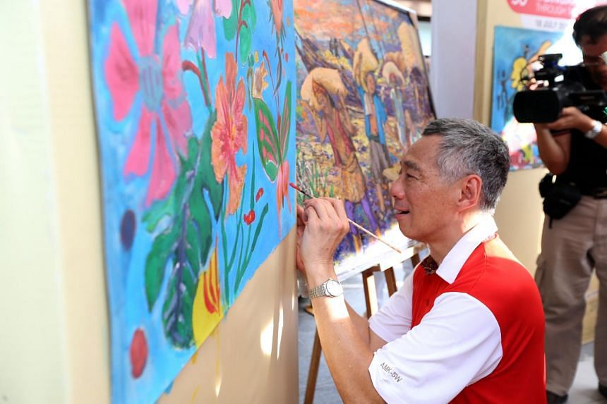 PM Lee adding the finishing touches to a canvas painting.
