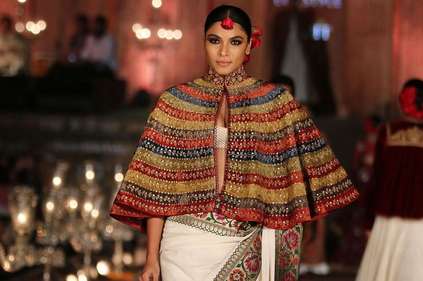 Designer Rohit Bal uses a softer fabric for the Benares sari to woo younger women to buy and wear it. Designer Ritu Kumar working with a weaver. She is one of 50 designers who are helping to revive and modernise the sari industry.