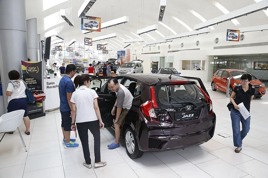Customers at the Honda showroom in Alexandra Road yesterday. Some showrooms reported an increase in the number of walk-in customers. Prices of new cars have fallen as COE prices drop to their lowest in at least five months in the latest COE tender on
