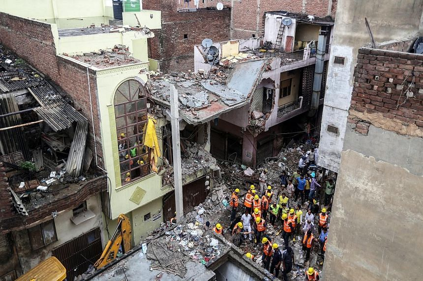Rescue workers sifting debris at what used to be a four-storey building in the Vishnu Garden neighbourhood in western Delhi yesterday. The accident is the latest in a long line of deadly building collapses in India, some of which pointed to shoddy co