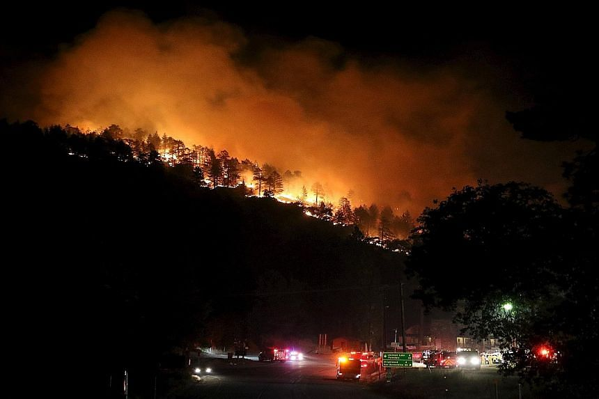 Los Angeles county firefighters battling a brush fire in Wrightwood, California, on Friday. The flames spilled onto a busy highway linking Los Angeles and Las Vegas, destroying several dozen cars and trucks abandoned by their fleeing owners. Televisi