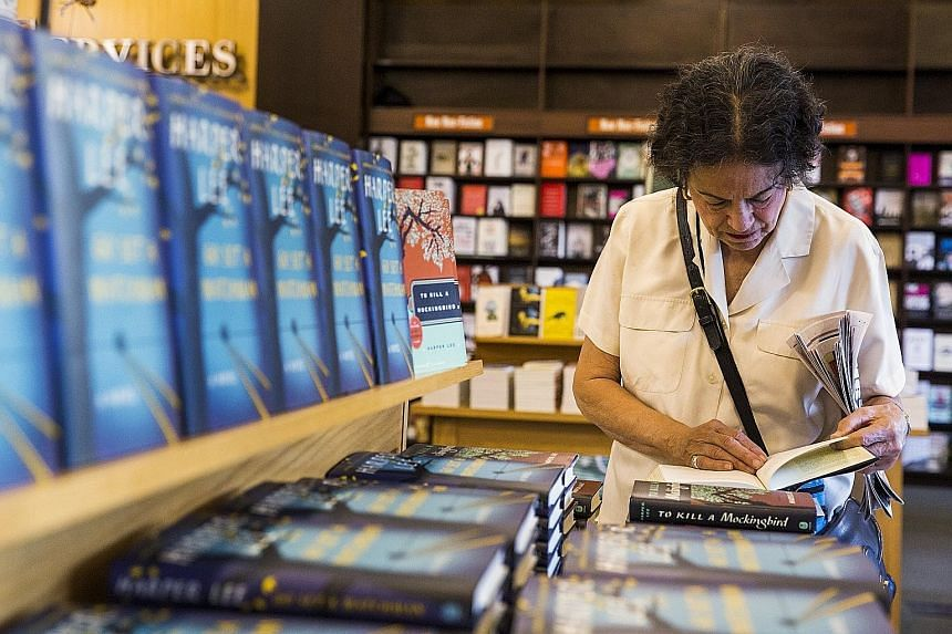 A woman looking through To Kill A Mockingbird before buying a copy of Harper Lee's book Go Set A Watchman in New York.