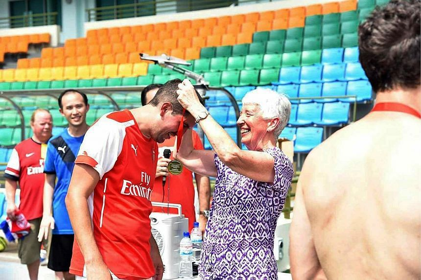 Jill Smith presenting a medal to one of the winners of a fans' football tournament organised by the Official Arsenal Singapore Supporters Club on Saturday. She helped establish more than 140 clubs worldwide.