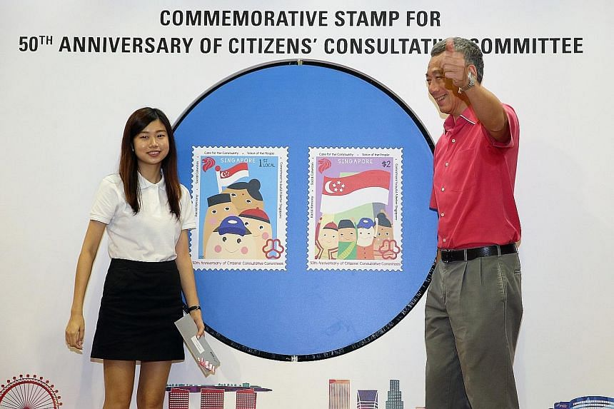 Prime Minister Lee Hsien Loong unveiling stamp designs commemorating the 50th Anniversary of the Citizens Consultative Committee yesterday. Ms Mavis Tan (left) from ITE College Central beat more than 90 other entries in a stamp design competition org