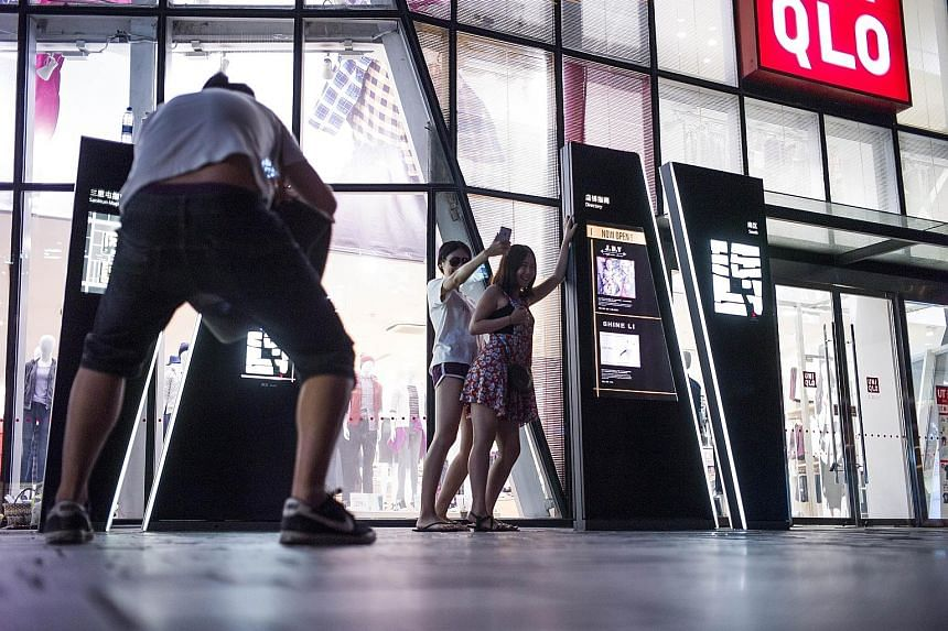 People posing in front of a Uniqlo store in Beijing, after a sex video shot in a fitting room of the chain went viral. A couple and three others were held over the incident.