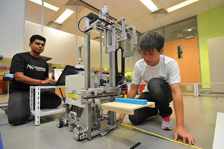Nanyang Polytechnic graduates Dinesh Mangalanathadurai (left), 19, and Lin Yong Qiang, 22, working on their robot at Nanyang Polytechnic. They will be taking part in the Mobile Robotics category in the WorldSkills competition in Brazil next month. Th