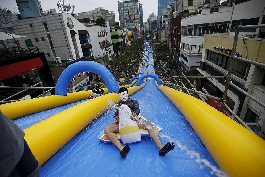 A man wearing a Guy Fawkes mask enjoying a ride on a 350m-long water slide during the City Slide Festa in Seoul yesterday. The water slide in the South Korean capital is the longest recorded in the country, local media said. And a local official said