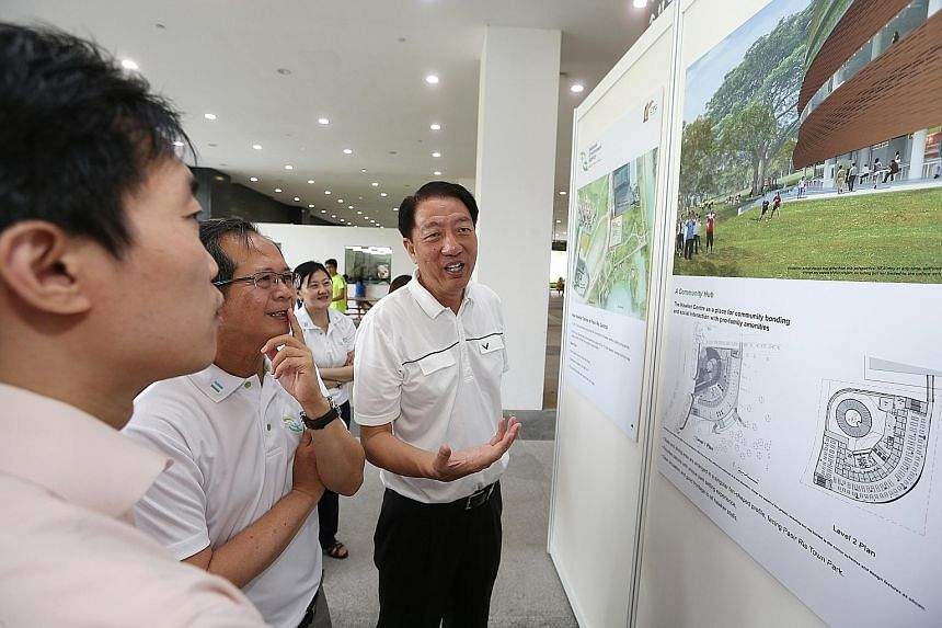 Deputy Prime Minister and MP for Pasir Ris-Punggol GRC Teo Chee Hean (right) looking at the new hawker centre's layout and artist's impressions during the ground-breaking ceremony yesterday.
