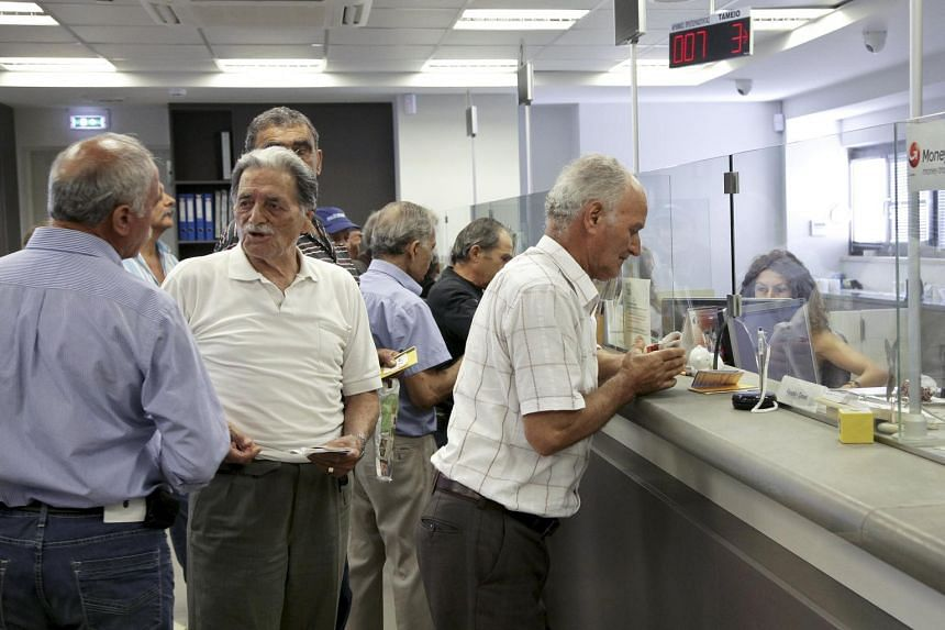 People make transactions at a counter inside a Piraeus Bank branch at the city of Iraklio in the island of Crete, Greece July 20, 2015. Greeks queued outside banks on Monday as they reopened three weeks after closing to stop the system collapsing und