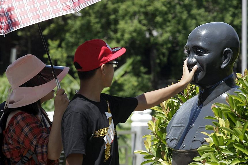 A person touches a bust of the late president and Nationalist leader Chiang Kai-shek in Taoyuan, northern Taiwan on July 5, 2015.