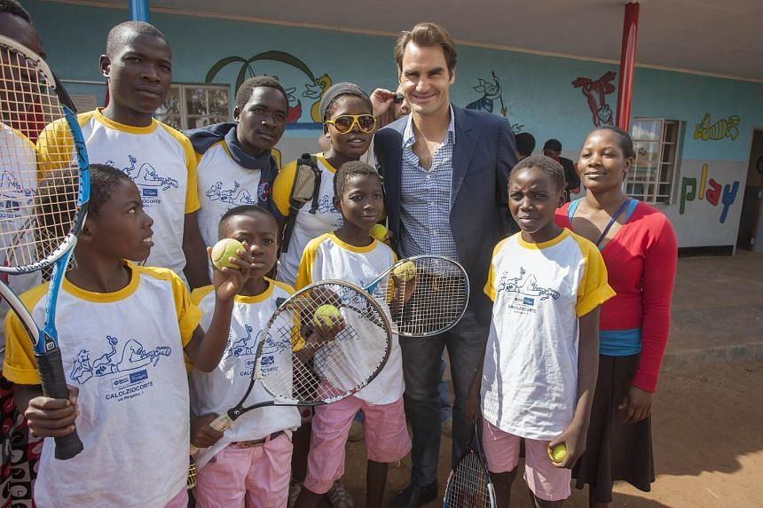 Roger Federer posing with children at the launch of the Lundu Community Childcare Centre in Malawai.