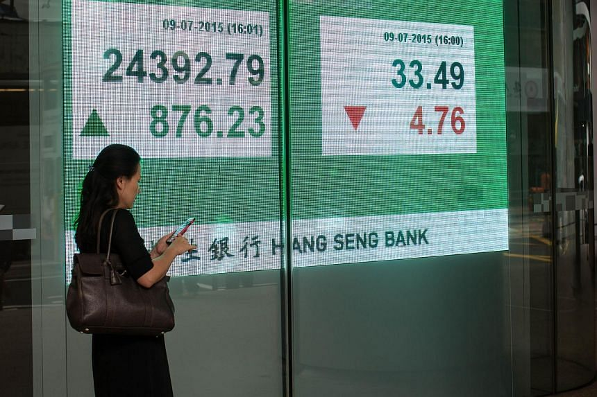 A woman using a smartphone stands near a screen displaying the Hang Seng Index figure, left, outside the Hang Seng Bank Ltd. headquarters in Hong Kong.