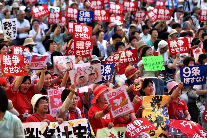Civic group members hold placards and chant anti-government slogans in Tokyo on July 14, 2015 to protest against Prime Minister Shinzo Abe's controversial security bills.