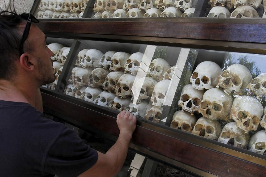 """A tourist looks at the skulls and bones of more than 8,000 victims of the Khmer Rouge regime that are displayed at Choeung Ek, a """"Killing Fields"""" site located on the outskirts of Phnom Penh, on July 2, 2015."""