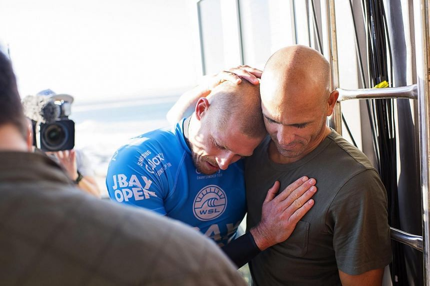 Mick Fanning being hugged by fellow competitor Kelly Slater of the US following the shark attack.