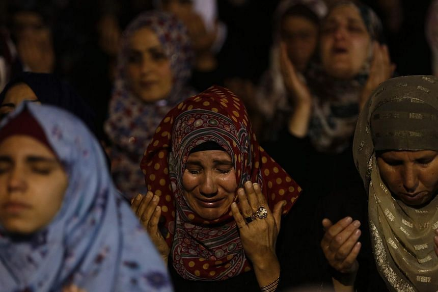 Palestinian worshippers pray the 'Tarawih' prayer before they attend Laylat Al Qadr, also known as the Night of Power outside the Dome of the Rock at the al-Aqsa mosque compound in Jerusalem on July 13, 2015.