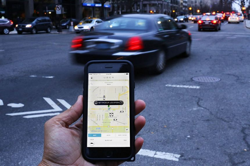 File photograph of an Uber application as cars drive by in Washington, DC.