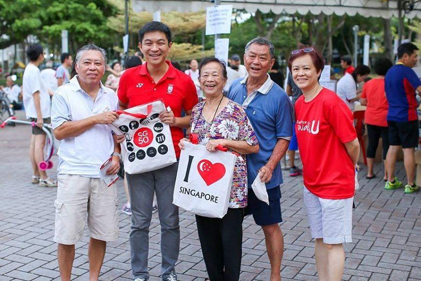 Minister for Social and Family Development Tan Chuan Jin with residents who collected their SG 50 fun packs.