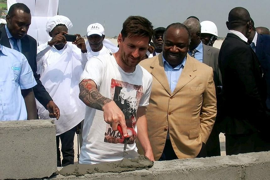 Lionel Messi, accompanied by Gabon President Ali Bongo Ondimba, laying the first stone at a future African Cup of Nations venue in Port-Gentil on Saturday. He is not in the United States for Barcelona's pre-season tour, having been given an extended