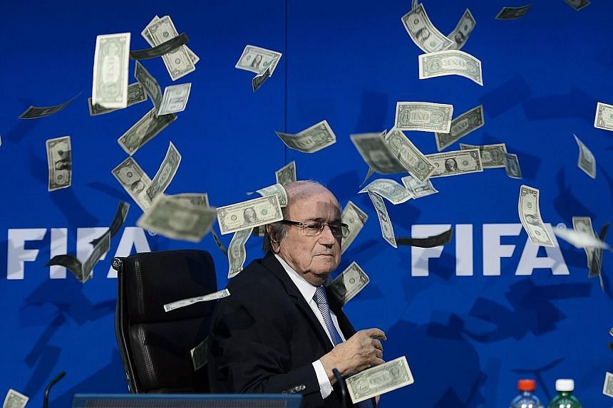 A clearly unimpressed Fifa president Sepp Blatter looking at fake dollar bills flying around him during a press conference at the football world body's headquarters in Zurich. The notes were thrown by a protester.