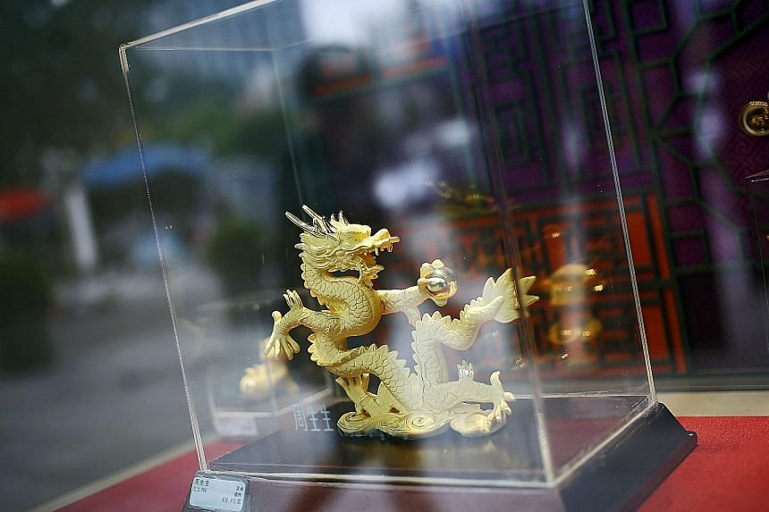 A gold dragon in a jewellery store in Beijing. Heavy selling on the Shanghai Gold Exchange and New York's Comex yesterday morning sent gold tumbling, before it stabilised at US$1,110 in the evening.