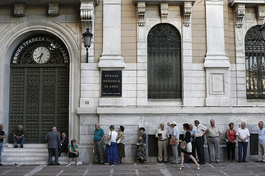 A stallholder waiting for customers in Athens' central market yesterday as Greeks woke up to widespread price hikes, part of a cash-for-reform deal with the country's creditors. Customers waiting for a National Bank of Greece branch in Athens to open