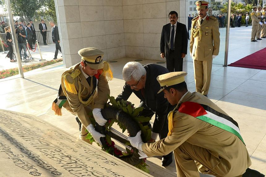 Palestinian President Mahmoud Abbas lays a wreath at the grave of late Palestinian leader Yasser Arafat on the first day of Eid al-Fitr holiday, in Ramallah on July 17, 2015.