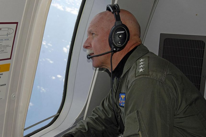 Admiral Scott Swift, commander of the US Pacific Fleet, observes operations aboard a P-8A Poseidon aircraft during a flight hosted by the Pelicans of Patrol Squadron (VP) 45 in the South China Sea on July 18, 2015.