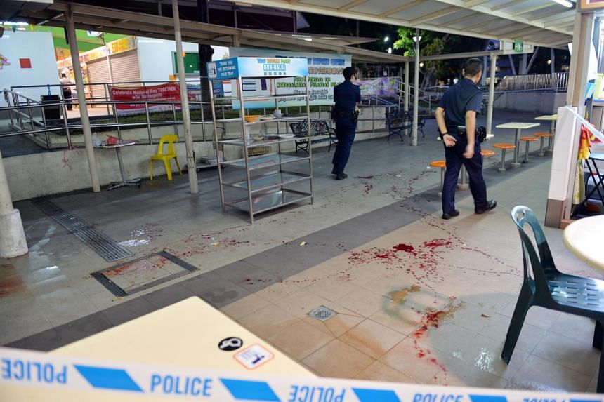 Police officers stand near a trail of blood in Bedok North hawker centre after a man who was slashed ran in.