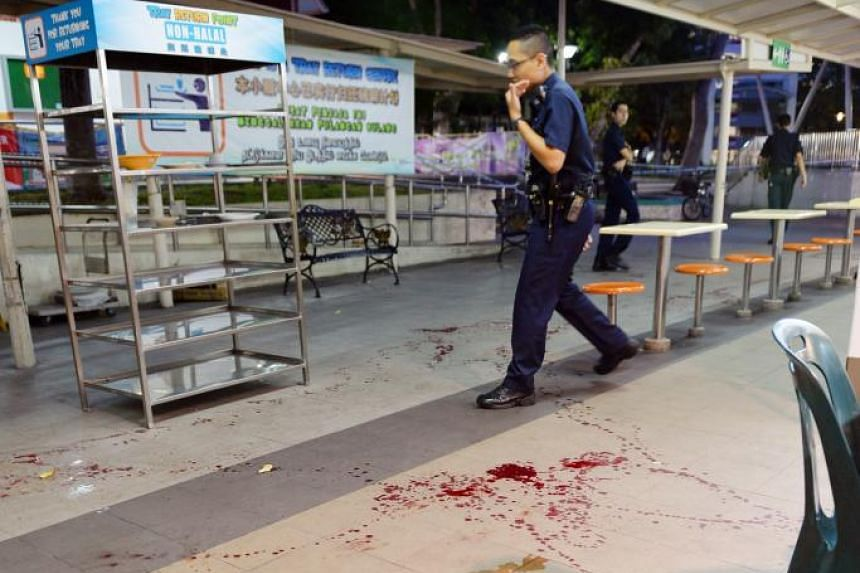 Police officers standing near a trail of blood in Bedok North hawker centre during investigations in a slashing case.