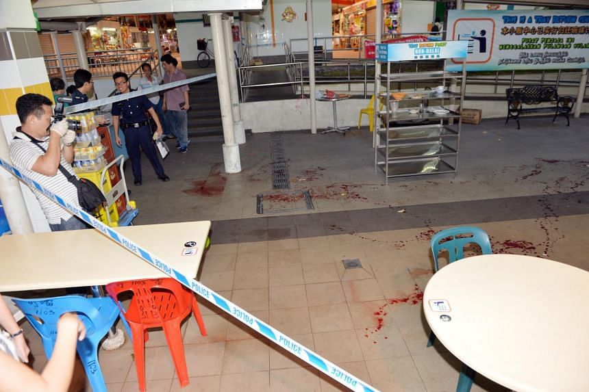 Investigators at Bedok North hawker centre looking at the trail of blood left by the victim of a slashing incident.