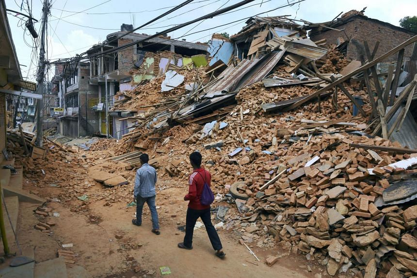 Nepalese residents walk past destroyed buildings after two earthquakes shook the country, in Chautara in north-eastern Nepal, on May 13, 2015.
