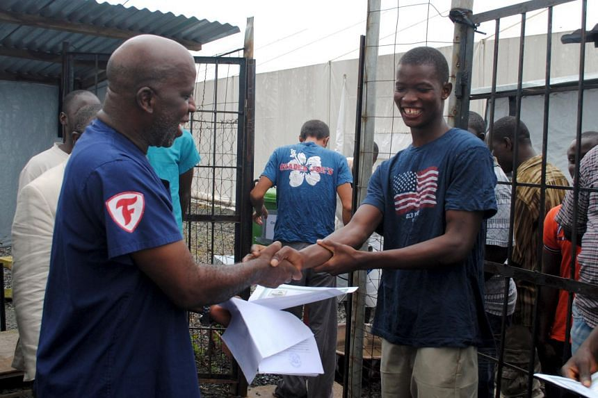 Liberian Cassius Kollie (right), 24, one of the four Ebola patients discharged.