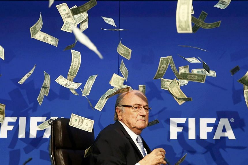 British comedian Lee Nelson (unseen) throws banknotes at Fifa President Sepp Blatter as he arrives for a news conference after the Extraordinary Fifa Executive Committee Meeting.