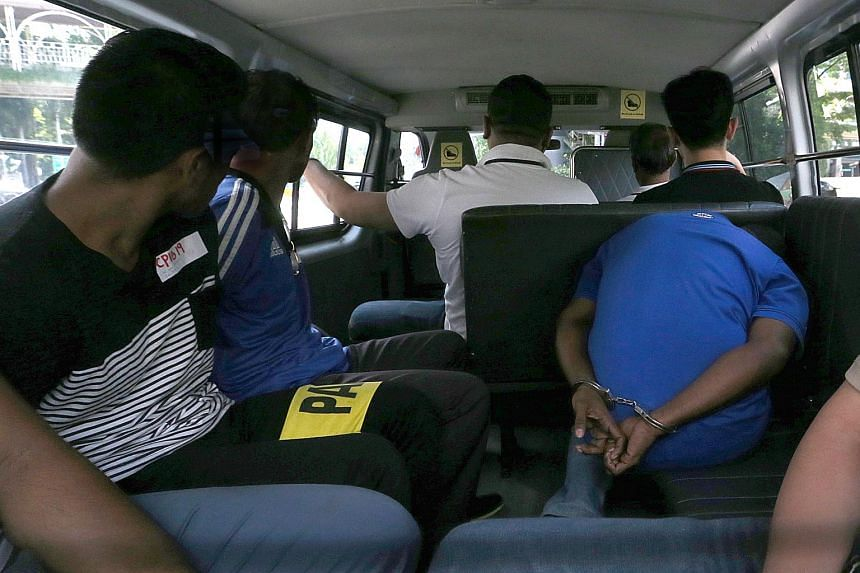 Former Timor Leste footballer Moises Natalino de Jesus, Rajendran Kurusamy and his associate, Indonesian national Nasiruddin, leaving the State Courts in a van on May 30, 2015.