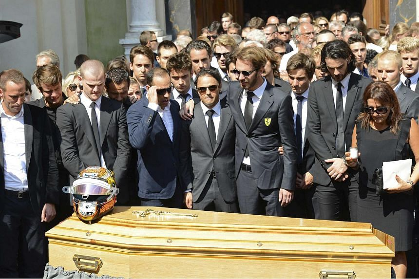 Friends and relatives, including F1 drivers Jean-Eric Vergne (fourth from right) and Felipe Massa (centre), gathering around Bianchi's coffin.