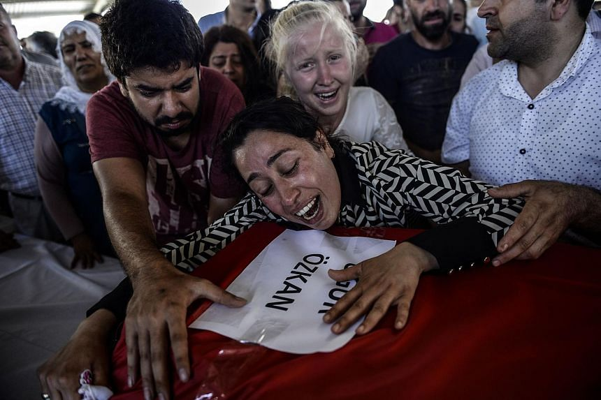 Mourners cry over a coffin in Gaziantep during a funeral ceremony for victims following a suicide bomb attack the day before which killed at least 31 in the southern Turkish town of Suruc, on July 21, 2015.