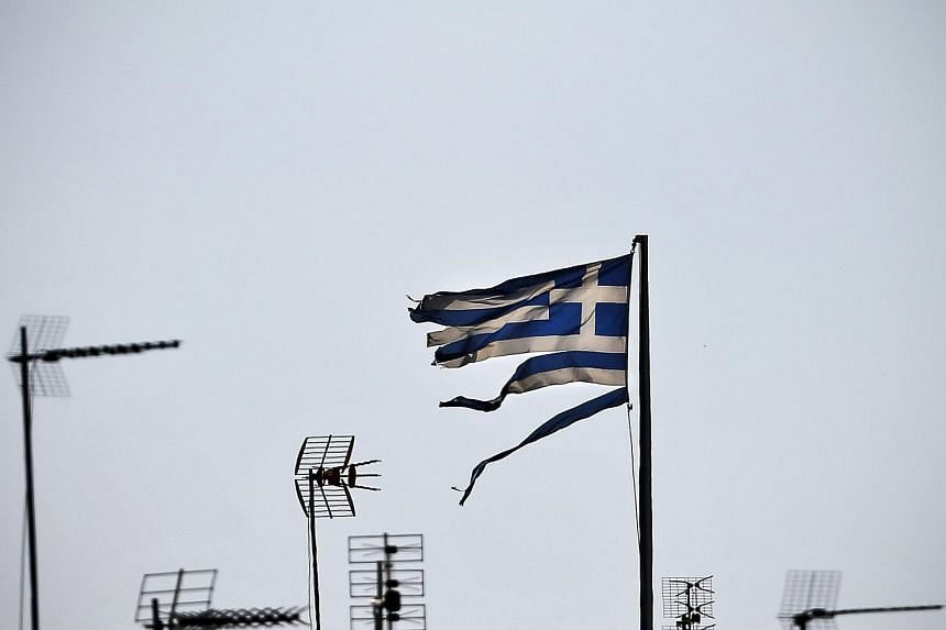 A frayed Greek national flag flutters among antennas atop a building in central Athens, Greece on July 20, 2015.