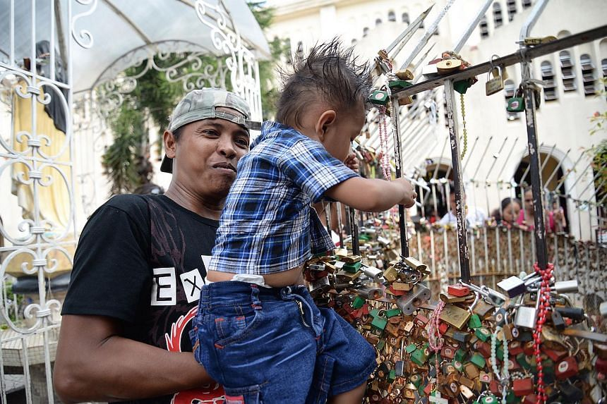 A man hoisting his child up the fence surrounding the grotto.