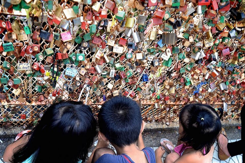 """Children checking out thousands of """"love locks"""" surrounding the grotto."""