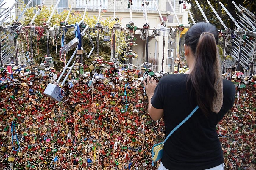 """A wall of """"love locks"""" surrounding a grotto in a city south of Manila."""