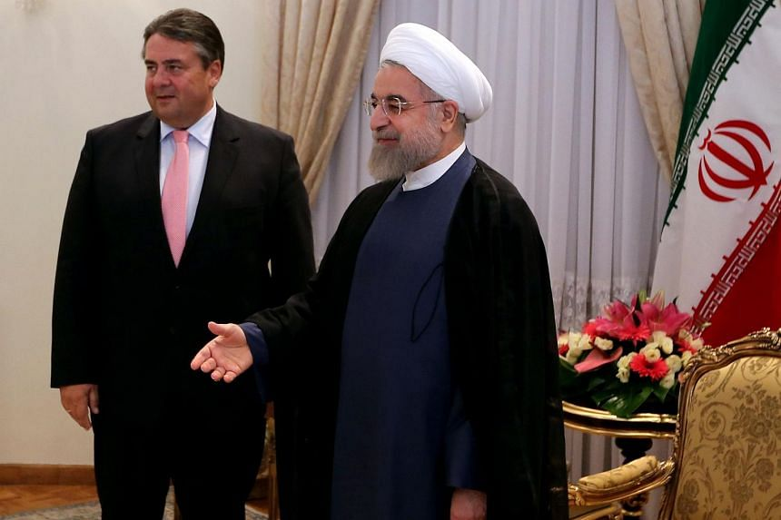 Iranian President Hassan Rouhani stands next to German Economy and Energy Minister Sigmar Gabriel (left) in Tehran on July 20, 2015.
