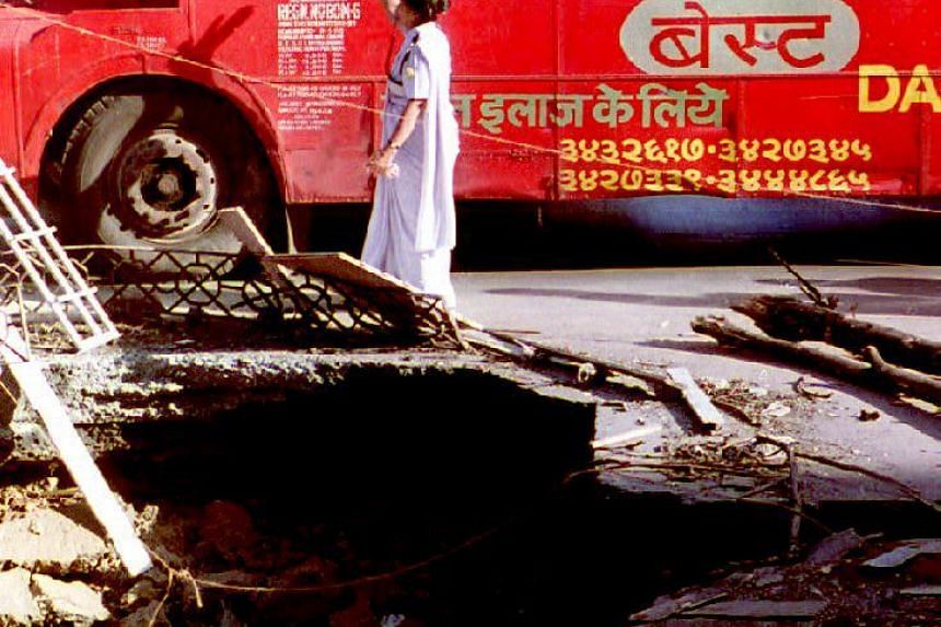 A bus drives past a crater caused during the March 12 bomb attacks in Mumbai, India, in this March 13, 1993 file photo.