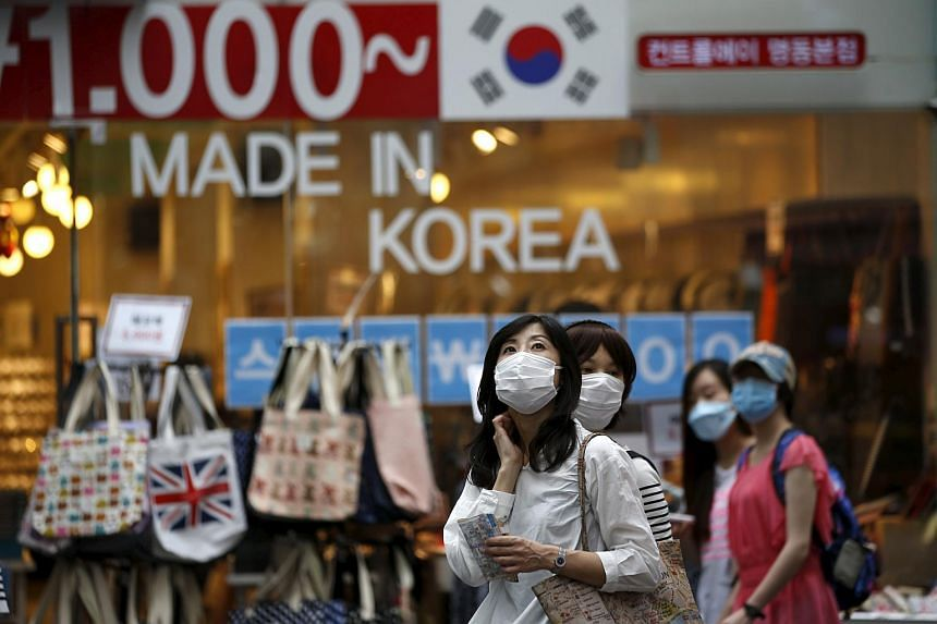 Tourists wearing masks to prevent contracting Middle East Respiratory Syndrome (Mers) look around Myeongdong shopping district in central Seoul, South Korea.