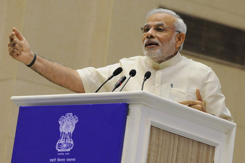 """Indian Prime Minister Narendra Modi gestures as he addresses a ceremony at the launch of """"Smart Cities Mission, Atal Mission for Rejuvenation and Urban Transformation (AMRUT)' in New Delhi on June 25, 2015."""