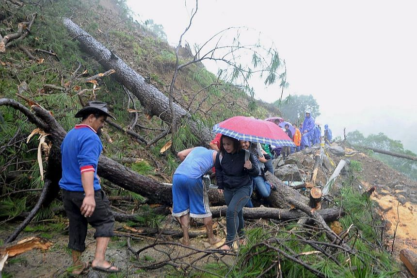 Residents walk on a road covered with debris after landslides brought on by torrential monsoon rains, killed two people in northern Philippines on July 13, 2015.